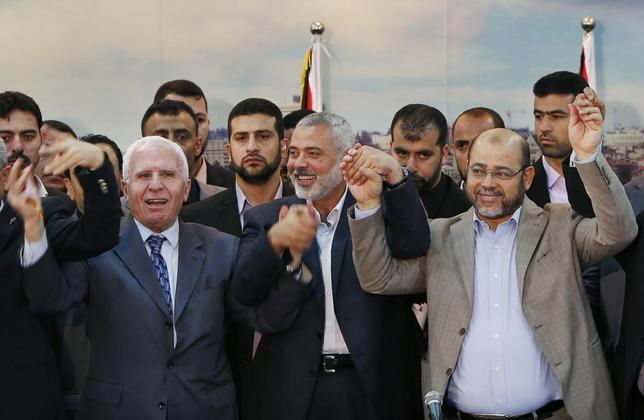 Senior Fatah official Azzam Al-Ahmed (L), head of the Hamas government Ismail Haniyeh (C) and senior Hamas leader Moussa Abu Marzouq hold their hands after announcing a reconciliation agreement in Gaza City April 23, 2014. REUTERS/Suhaib Salem