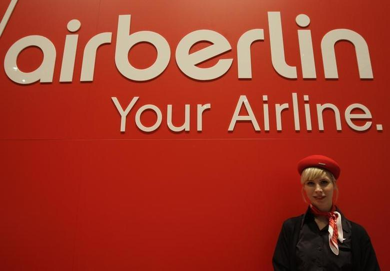 A woman stands behind the exhibition stand of Air Berlin at the ITB tourism fair in Berlin, March 11, 2009. REUTERS/Tobias Schwarz