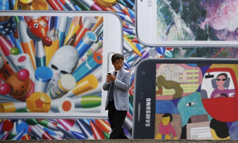 A man uses his mobile phone in front of a giant advertisement promoting Samsung Electronics' new Galaxy S5 smartphone, at an art hall in central Seoul April 15, 2014. REUTERS/Kim Hong-Ji
