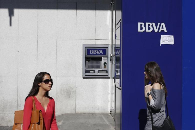 Two women walk past a BBVA bank branch in Madrid October 11, 2013. REUTERS/Juan Medina