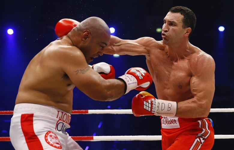 World heavyweight boxing champion Vladimir Klitschko of Ukraine lands a punch to defeat Australian challenger Alex Leapai (L) during their WBO heavyweight title fight in Oberhausen April 26, 2014. Klitschko won after knock out in round six. REUTERS/Kai Pfaffenbach