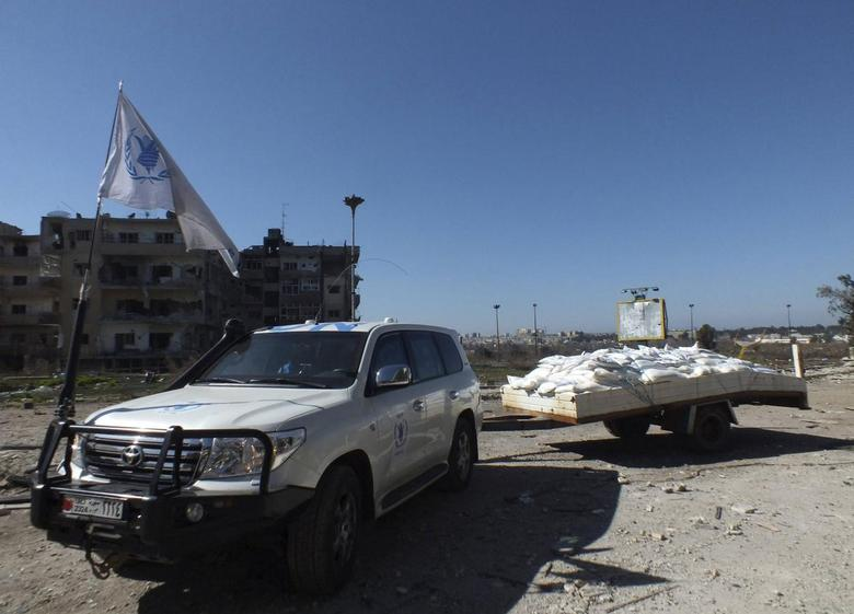 A United Nations vehicle towing a trailer with humanitarian aid arrives at a besieged area of Homs February 12, 2014. REUTERS/Yazan Homsy