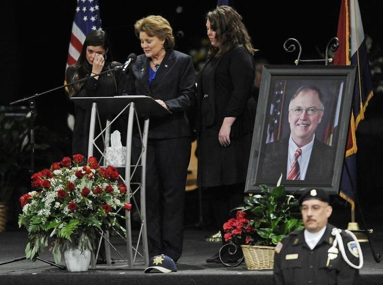 Lisa Clements, the widow of chief executive of the Colorado Department of Corrections, Tom Clements, is supported by her daughters Sara (L) and Rachel as she speaks at his memorial at New Life Church in Colorado Springs, Colorado, March 25, 2013. REUTERS/Jerilee Bennett/The Gazette/Pool