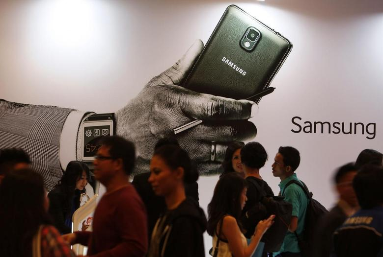 People gather in front of an ad during the launch of the Samsung Galaxy Note 3 and Galaxy Gear in Jakarta, September 26, 2013. REUTERS/Beawiharta