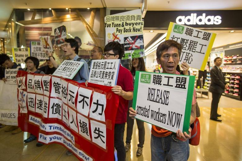 Protesters from labour organizations shout slogans in support of the strike by workers at a Yue Yuen Industrial Holdings Ltd shoe factory complex in Dongguan, at a shopping mall in Hong Kong April 24, 2014. REUTERS/Tyrone Siu