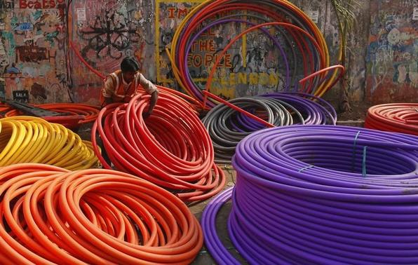 A labourer works amid rolls of underground telephone cable pipes on the side of a road in Mumbai January 9, 2014. REUTERS/Danish Siddiqui/Files