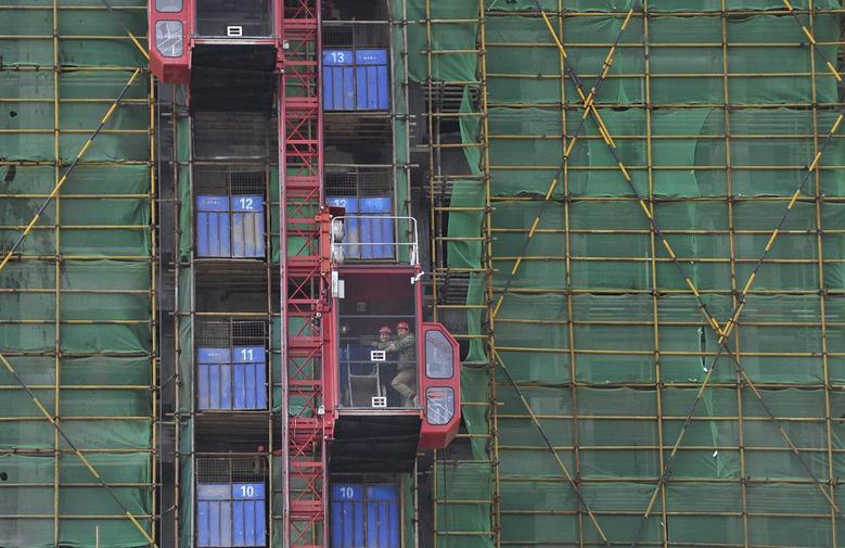 Labourers take a lift at the construction site of new residential buildings in Hefei, Anhui province, April 28, 2014. REUTERS/Stringer