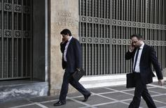 Two men speak on their phones as they walk outside the Bank of Greece in Athens April 9, 2014. REUTERS/Yorgos Karahalis