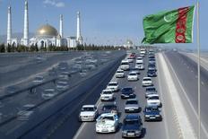 Машины проезжают мимо флага Туркмении недалеко от мавзолея Сапармурада Ниязова близ Ашхабада 19 февраля 2009 года. Туркмения отменила бесплатную раздачу до 120 литров бензина в месяц на жителя страны, объяснив стремлением упорядочить местный рынок нефтепродуктов, подконтрольный государству. REUTERS/Stringer