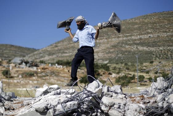 A Palestinian man holds damaged loudspeakers belonging to a mosque after it was demolished by Israeli bulldozers in Khirbet Al-Taweel village near the West Bank City of Nablus April 29, 2014. REUTERS-Mohamad Torokman
