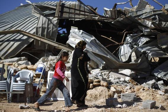 Palestinians walk past a structure after it was demolished by Israeli bulldozers in Khirbet Al-Taweel village near the West Bank City of Nablus April 29, 2014. REUTERS-Mohamad Torokman