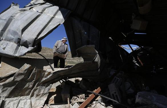 A Palestinian man inspects a structure after it was demolished by Israeli bulldozers in Khirbet Al-Taweel village near the West Bank City of Nablus April 29, 2014. REUTERS-Mohamad Torokman