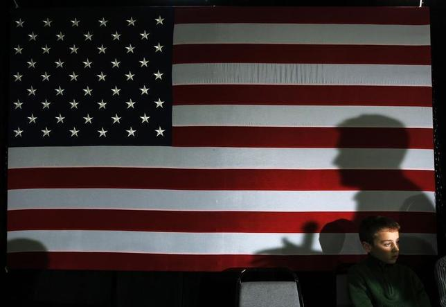 Republican presidential candidate and former Massachusetts Governor Mitt Romney casts a shadow on a U.S. flag while speaking at a ''We the People Freedom Forum'' in Hudson, New Hampshire December 11, 2011. REUTERS/Brian Snyder