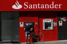 Un hombre usa un cajero automático en una sucursal del banco Santander en Madrid, sep 16 2013. El Banco Santander de España sorprendió el martes a los mercados con la oferta para comprar el 25 por ciento que no controla de su filial brasileña, por un valor de 4.686 millones de euros a pagar con acciones propias. REUTERS/Juan Medina