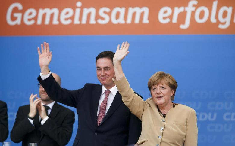 German Chancellor Angela Merkel, leader of the Christian Democratic Union (CDU), waves next to CDU's top candidate for European parliamentary elections David McAllister (L) during an election campaign in Bremerhaven April 29, 2014. REUTERS/Ina Fassbender