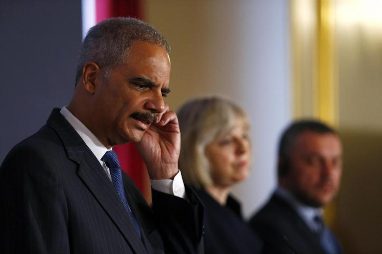 (From L to R) U.S. Attorney General Eric Holder scratches his ear as he answers a question during a news conference with Britain's Home Secretary Theresa May and Ukraine's acting Prosecutor General Oleh Makhnitsky at the Ukraine Forum on Asset Recovery at Lancaster House in central London, April 29, 2014. REUTERS/Andrew Winning