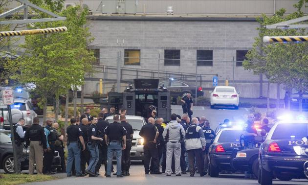 Police officers from Cobb County Police, and Marietta and Kennesaw departments stage near the entrance of the Federal Express Ground building after a man opened fire inside the building before turning the gun on himself in Kennesaw, Georgia, April 29, 2014. REUTERS-Kelly J. Huff-Marietta Daily Journal