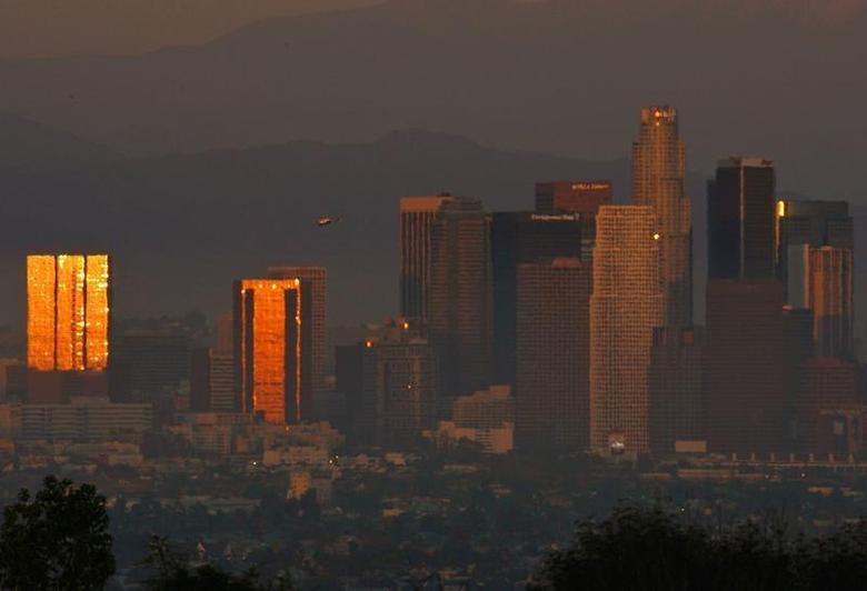 The sun reflects on downtown skyscrapers as it sets through the Los Angeles smog and haze, October 22, 2006. REUTERS/Lucy Nicholson