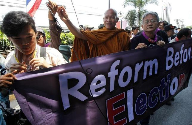 Thai Buddhist monk and protest leader Luang Pu Buddha Issara gestures as his supporters hold a banner during a rally outside a hotel in Bangkok April 22, 2014. REUTERS/Chaiwat Subprasom