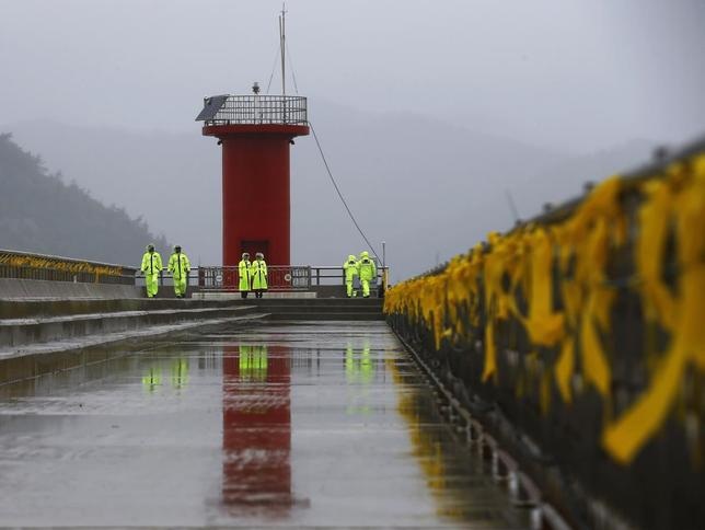 Police officers stand guard at a pier, as yellow ribbons dedicated to missing and dead passengers on board the capsized Sewol ferry are tied to its handrails, at a port where family members are waiting for news from the search and rescue team in Jindo, April 28, 2014. REUTERS/Kim Kyung-Hoon