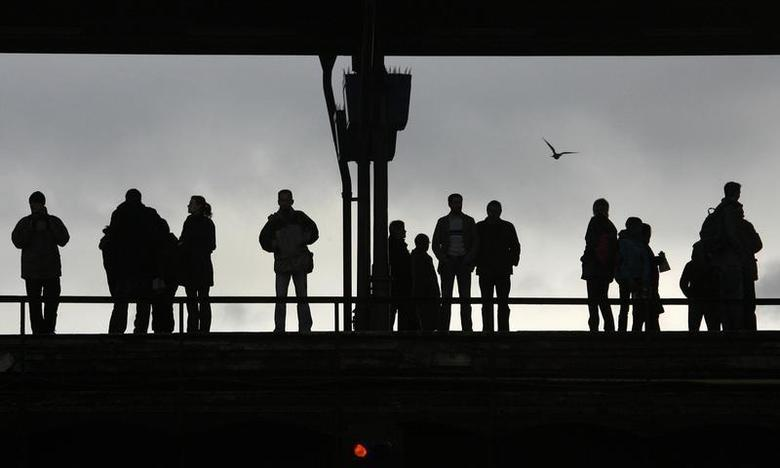 Commuters are silhouetted as they wait for a city train on the platform in a railway station in Berlin November 14, 2007. REUTERS/Fabrizio Bensch