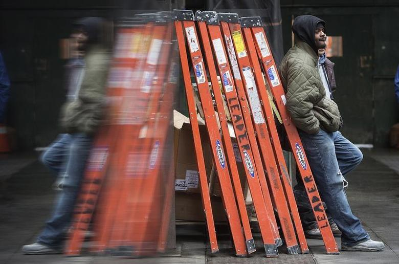 A worker is reflected on a shiny wall as he leans against some orange ladders in the Manhattan borough of New York February 21, 2014. REUTERS/Carlo Allegri