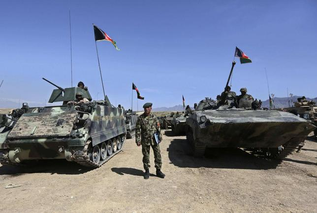 An Afghan National Army officer stands among tanks before a military exercise on the outskirts of Kabul April 30, 2014. REUTERS/Omar Sobhani