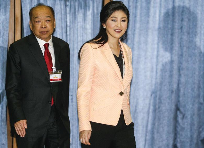 Thailand's Prime Minister Yingluck Shinawatra (R) and Deputy Prime Minister Surapong Tovichakchaikul arrive before a meeting with the Election Commission at the Royal Thai Air Force Academy in Bangkok April 30, 2014. REUTERS/Athit Perawongmetha
