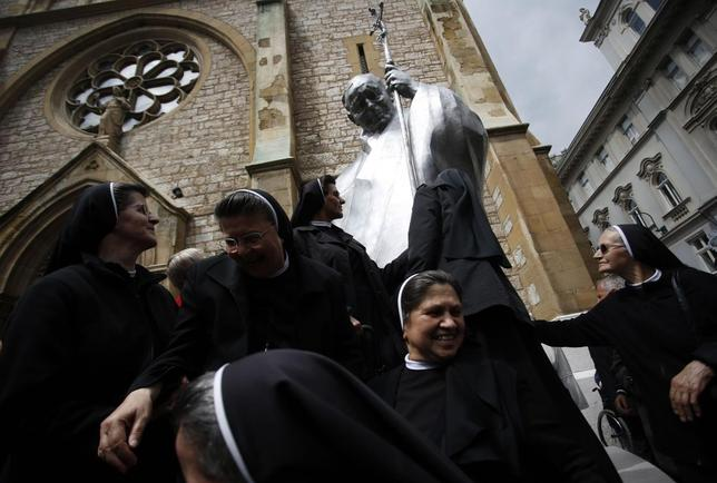 Nuns touch a statue of the late Pope John Paul II after it was erected in Sarajevo April 30, 2014. REUTERS/Dado Ruvic