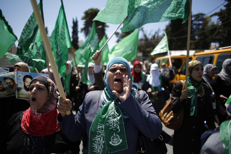 Palestinian women wave Hamas flags as they take part in the funeral of leading Hamas militants Imad and Adel Awadallah, who were killed by Israeli forces during a raid on their hideout in 1998, in the West Bank town of Al-Bireh April 30, 2014. REUTERS/Mohamad Torokman