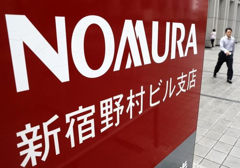 A man walks next to a sign for Nomura Securities in Tokyo July 25, 2013. REUTERS/Yuya Shino