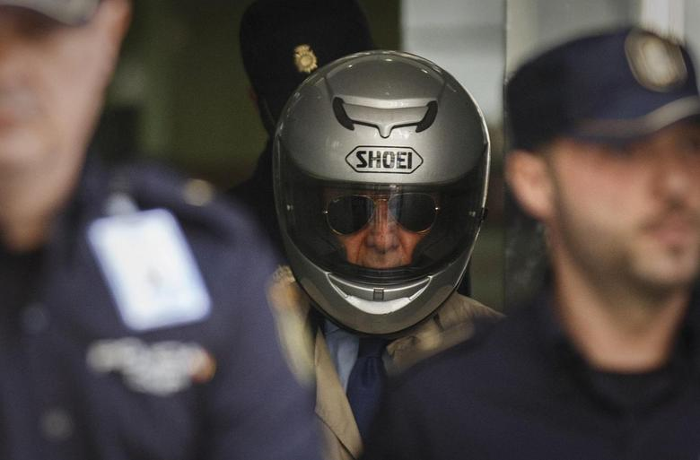 Former police inspector Juan Antonio Gonzalez Pacheco, known as ''Billy the Kid,'' leaves Madrid's High Court in Madrid wearing a motorcycle helmet after appearing before a judge at an extradition hearing April 10, 2014. REUTERS/Andrea Comas