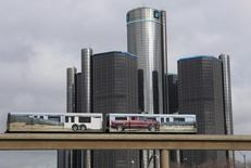 Two cars of the 'people mover' public rail are seen covered with a advertisement for the 2014 Chevy Silverado pickup truck as they move past General Motors World Headquarters in Detroit, Michigan January 11, 2013. REUTERS/Rebecca Cook