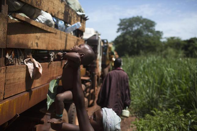 A woman passes her child on the top of a truck during a break from her journey towards Chad's border escorted by African Union operation in CAR (MISCA) a few kilometres after the northern town of Kaga Bandoro April 29, 2014. REUTERS/Siegfried Modola