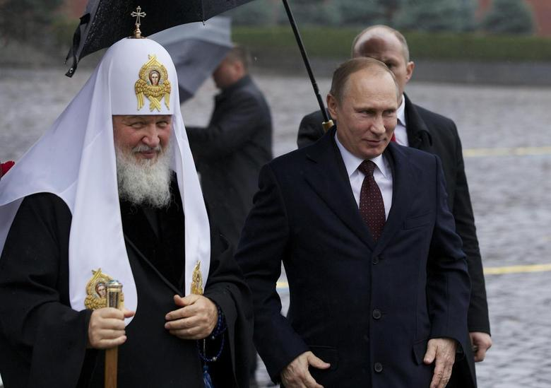 Russian President Vladimir Putin (R) and Patriarch Kirill of Moscow and All Russia walk to lay flowers at a monument of Minin and Pozharsky, the leaders of a liberation struggle against foreign invaders in 1612, on National Unity Day in Red Square in Moscow, November 4, 2013. REUTERS/Alexander Zemlianichenko/Pool