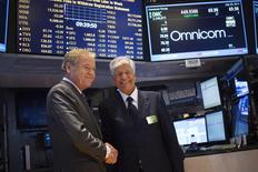Omnicom Chief Executive John Wren (L) and Publicis Group Chairman and CEO Maurice Levy shake hands after announcing an agreement on their merger on the floor of the New York Stock Exchange in New York in this July 29, 2013, file photo. REUTERS/Shannon Stapleton/Files
