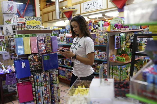 Store employee Ashley Beal takes an order via a smartphone app to be delivered to the customer by a Google car and courier at a toy and sporting goods shop in Palo Alto, California March 17, 2014. REUTERS/Robert Galbraith