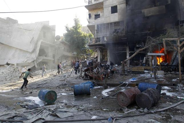 Residents run after, according to activists, two barrel bombs were thrown by forces loyal to Syria's president Bashar Al-Assad in Hullok neighbourhood of Aleppo May 1, 2014. REUTERS/Jalal Al-Mamo
