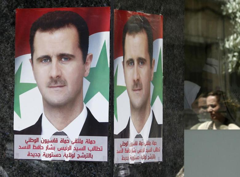 Posters of Syrian President Bashar al-Assad placed by pro-Assad group ''Qasion Forum'', calling for him to run for a third term, are seen at a street in Damascus April 28, 2014. REUTERS/Khaled al-Hariri