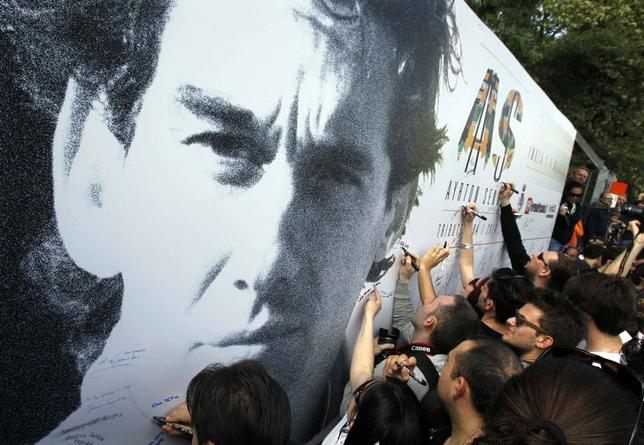 People sign a board with an image of Brazilian Formula One driver Ayrton Senna during a memorial at the Imola race track, northern Italy May 1, 2014. REUTERS/Alessandro Garofalo