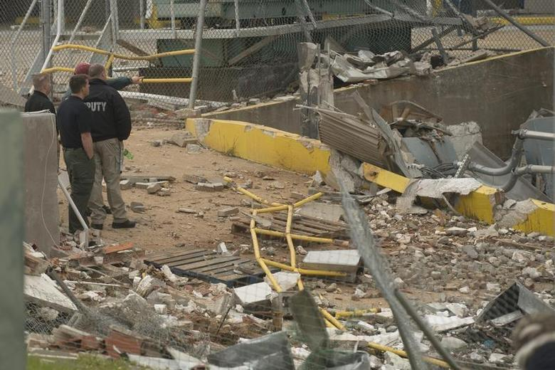 Investigators survey the damage after an apparent gas explosion killed 2 and injured over 100 inmates and guards at Escambia County jail in Pensacola, Florida May 1, 2014. REUTERS/Michael Spooneybarger