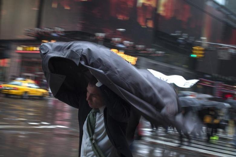 A man uses his rain coat to guard against rain and wind as he commutes through Times Square, New York April 30, 2014. REUTERS/Adrees Latif