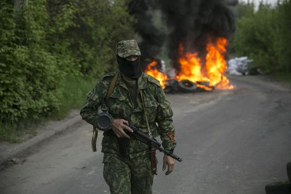 A pro-Russian separatist guards a checkpoint as tyres burn behind him near the town of Slaviansk in eastern Ukraine May 2, 2014. REUTERS/Baz Ratner