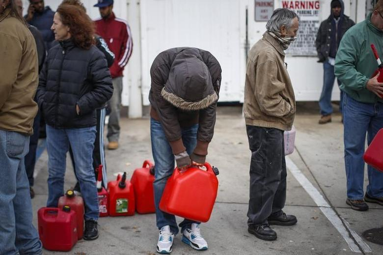 A man stands exhausted while waiting for over five hours to receive fuel from a gas station in Queens, a borough in New York which was left devastated by Hurricane Sandy November 1, 2012. REUTERS/Adrees Latif
