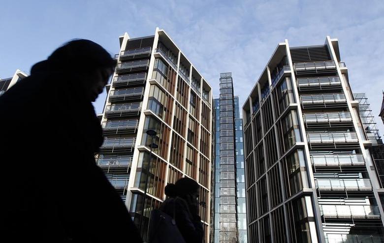 Pedestrians pass new development One Hyde Park in London January 19, 2011. REUTERS/Luke MacGregor