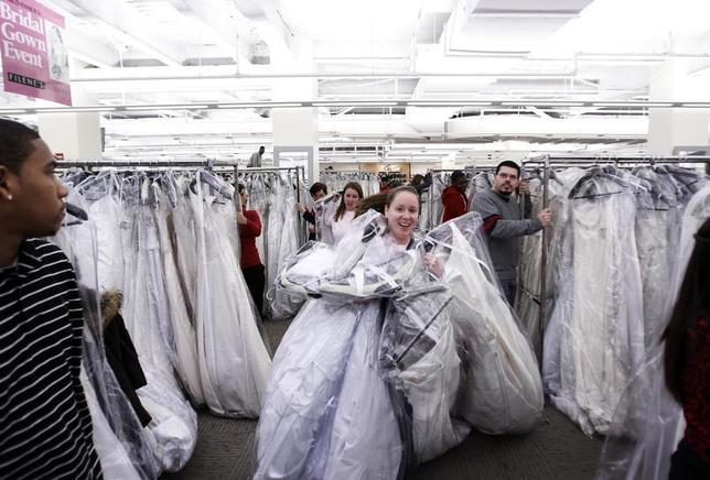 Shoppers fill their arms with wedding dresses at Filene's Basement during a ''Running of the Brides'' bridal dress sale in New York February 5, 2010. REUTERS/Lucas Jackson