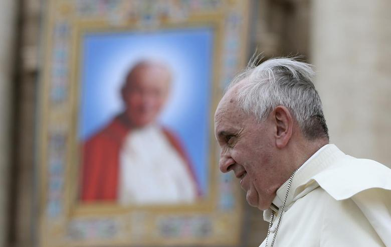 Pope Francis passes next to a tapestry of the late Pope John Paul II, as he leaves at the end of his weekly general audience at St. Peter's Square at the Vatican April 30, 2014. REUTERS/Alessandro Bianchi