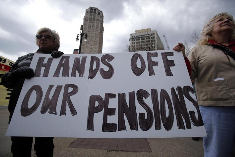 Two protestors hold a sign during a May Day protest against the Detroit Emergency Manager and the municipal Bankruptcy in downtown Detroit, Michigan May 1, 2014. REUTERS/Rebecca Cook