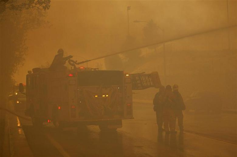 Firefighters protect homes as a wildfire driven by fierce Santa Ana winds blows in Rancho Cucamonga, California, April 30, 2014. REUTERS/David McNew