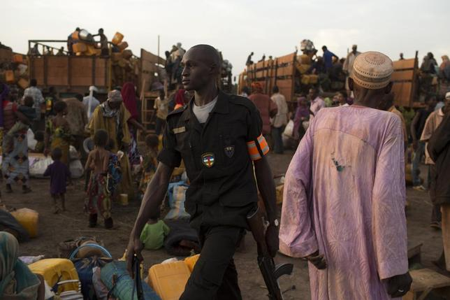 A local policeman guards an area as people disembark from trucks with their belongings at the transit IDP centre, after having travelled in a convoy escorted by the African Union operation in CAR (MISCA) on a four-day journey from the capital Bangui, on the outskirts of the Central African Republic-Chad border town of Sido April 30, 2014. REUTERS/Siegfried Modola